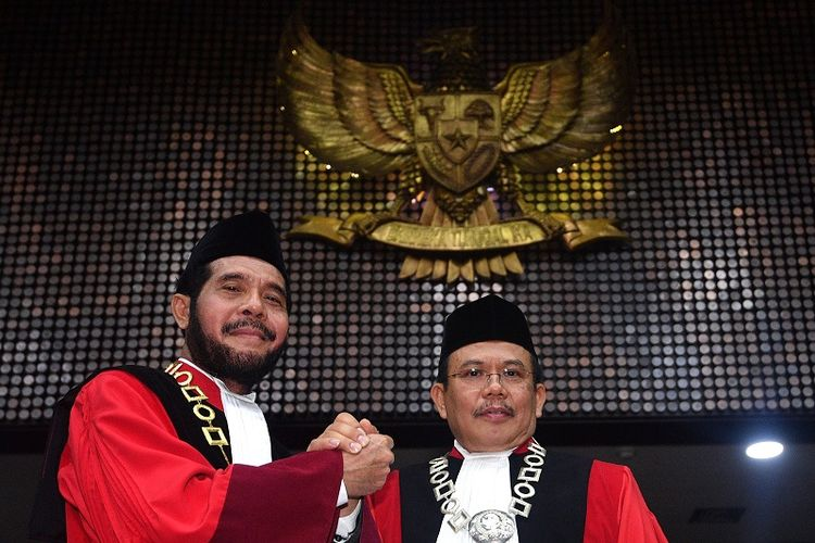 Ketua Mahkamah Konstitusi (MK) terpilih Anwar Usman (kiri) berjabat tangan dengan Wakil Ketua terpilih Aswanto usai acara pengucapan sumpah jabatan Ketua dan Wakil Ketua MK di gedung MK, Jakarta, Senin (2/4). Anwar Usman dan Aswanto resmi menjadi Ketua dan Wakil Ketua MK periode 2018-2020.