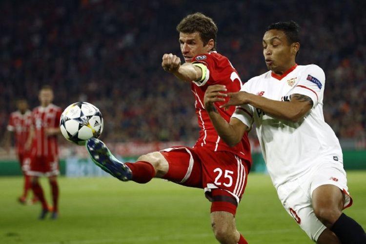 Thomas Mueller dan Luis Muriel berebut bola pada pertandingan perempat final Liga Champions antara Bayern Muenchen dan Sevilla di Stadion Allianz Arena, Rabu (11/4/2018).