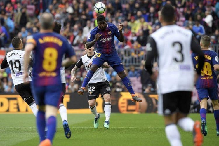Samuel Umtiti memenangi duel udara pada pertandingan La Liga Spanyol antara Barcelona dan Valencia di Stadion Camp Nou, Sabtu (14/4/2018).
