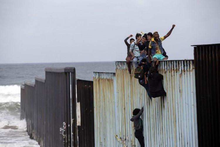 Aksi imigran memanjat pagar perbatasan antara AS-Meksiko di pantai Tijuana, dekat Samudra Pasifik, Minggu (29/4/2018). (AFP/Guillermo Arias)