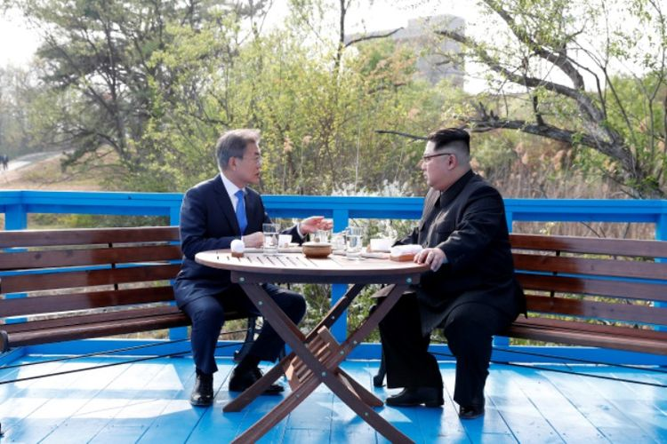 Presiden Korea Selatan Moon Jae In (kiri) ketika berbicara dengan Pemimpin Korea Utara Kim Jong Un di Panmunjom, saat Konferensi Tingkat Tinggi Antar-Korea Jumat (27/4/2018).