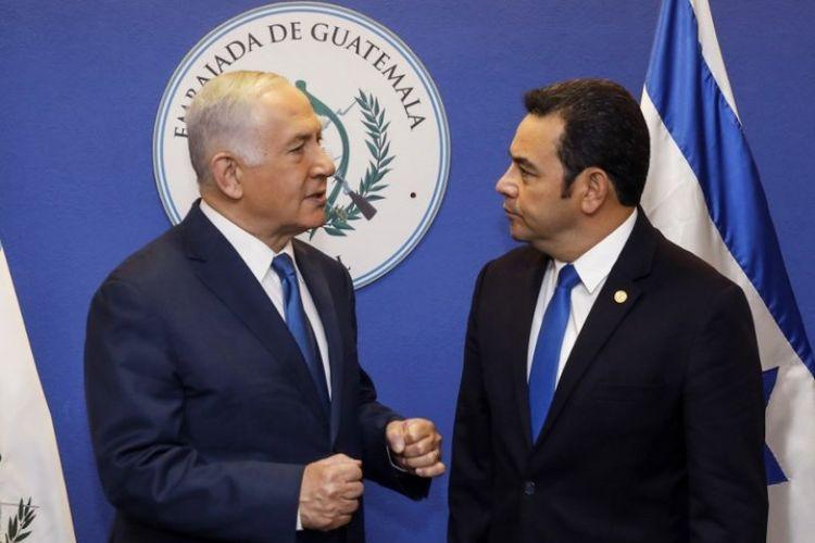 Perdana Menteri Israel Benjamin Netanyahu (kiri) dan Presiden Guatemala Jimmy Morales berbincang dalam acara pembukaan kedutaan besar Guatemala di Yerusalem, Rabu (16/5/2018). (AFP/Ronen Zvulun)