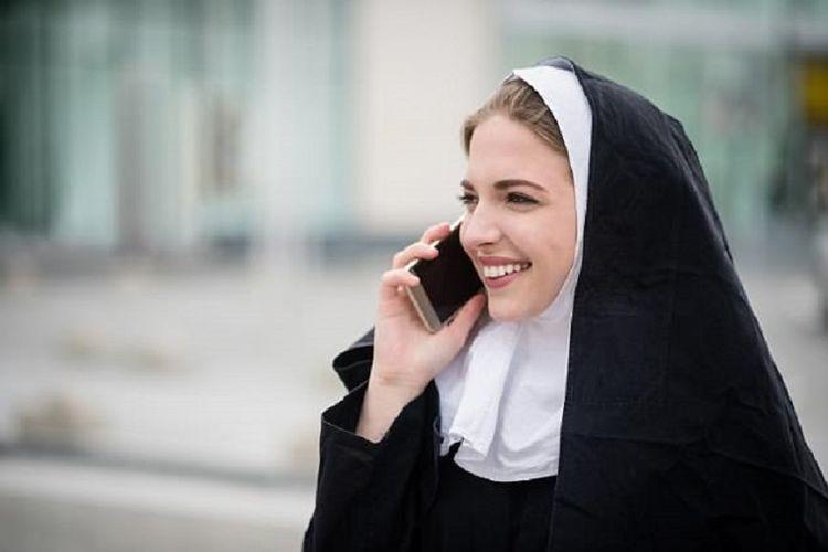 Seorang biarawati sedang menelepon menggunakan ponsel.