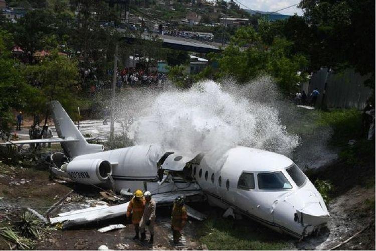 Pasukan pemadam kebakaran menyemprotkan busa ke tubuh pesawat yang terbelah setelah tergelincir di bandara Toncontin, Honduras untuk mencegah munculknya api.