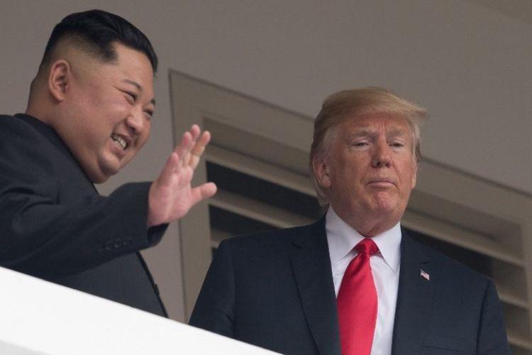 Pemimpin Korea Utara Kim Jong Un dan Presiden Amerika Serikat Donald Trump menyempatkan diri menyapa awak media di balkon Hotel Capella, Singapura, Selasa (12/6/2018). (AFP/Saul Loeb)