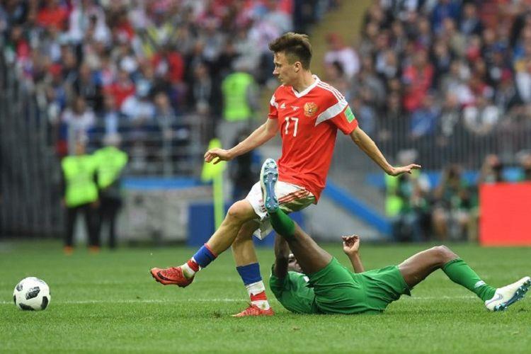 Gelandang Rusia, Aleksandr Golovin, mencoba melewati penjagaan bek Arab Saudi pada partai pembuka Piala Dunia 2018 di Stadion Luzhniki, 14 Juni 2018.