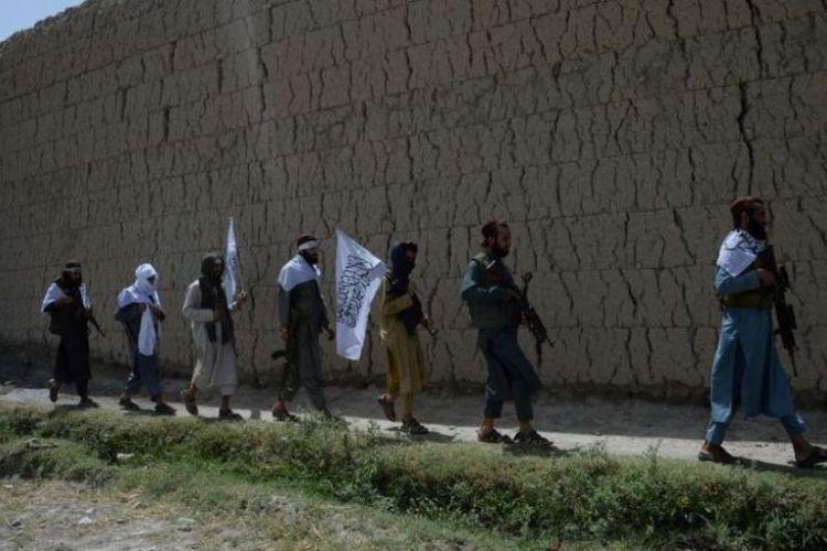 Pasukan Taliban di Afghanistan berjalan untuk merayakan gencatan senjata pada hari kedua Idul Fitri di pinggiran Jalalabad pada Sabtu (16/6/2018). (AFP/Noorullah Shirzada)