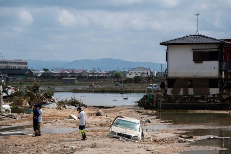 Penduduk memeriksa rumah mereka yang rusak akibat banjir di Mabi, Prefektur Okayama, Selasa (10/7/2018). (AFP/Martin Bureau)