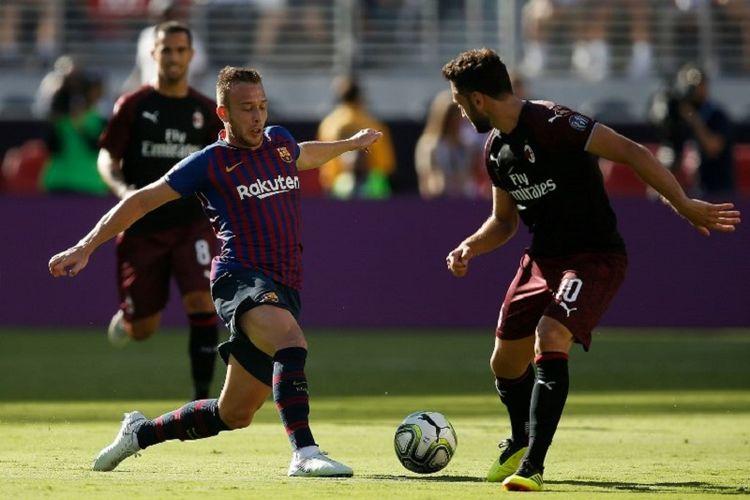 Arthur Melo mencoba melewati penjagaan Hakan Calhanoglu saat Barcelona berhadapan dengan AC Milan di Santa Clara, 4 Agustus 2018.