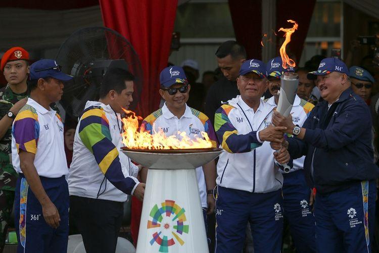Menteri Pertahanan Ryamizard Ryacudu (ketiga kanan) menyerahkan obor api Asian Games 2018 kepada Gubernur Sumatera Selatan Alex Noerdin (kanan) disaksikan Kapolri Jenderal Pol Tito Karnavian (tengah), Panglima TNI Marsekal Hadi Tjahjanto (kedua kanan), Ketua Umum Inasgoc Erick Thohir (kedua kiri) dan Ketua Panitia Pelaksana Daerah Asian Games 2018 Palembang Muddai Madang (kiri) saat pawai obor api Asian Games 2018 di Jakabaring Sport City (JSC), Palembang, Sumatera Selatan, Sabtu (4/8/2018). Obor api Asian Games 2018 tersebut dibawa mengelilingi kota Palembang dan menyusuri Sungai Musi, selanjutnya akan menuju sejumlah kabupaten/kota yang ada di Sumatera Selatan.