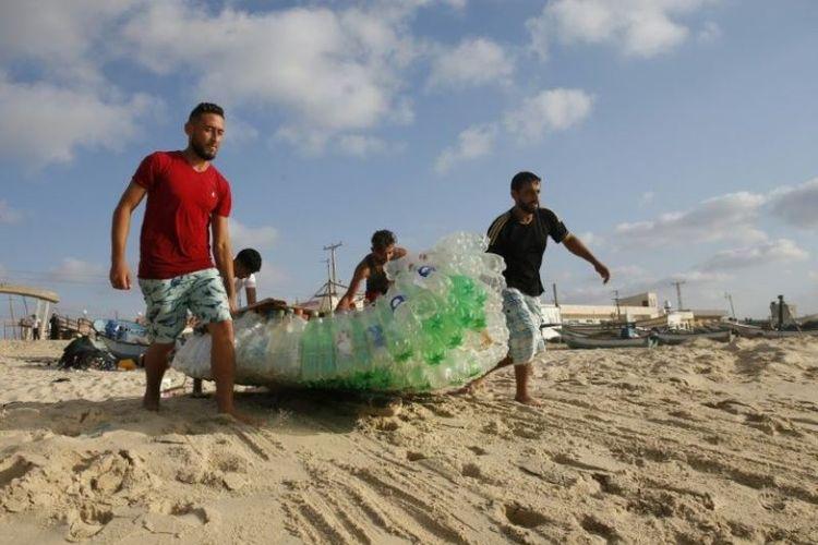 Nelayan Palestina bernama Mouad Abu Zeid (kanan) dan rekan-rekannya membawa perahu yang terbuat dari 700 botol plastik kosong di sebuah pantai di Rafah di Jalur Gaza selatan, Selasa (14/8/2018). (AFP/Said Khatib)