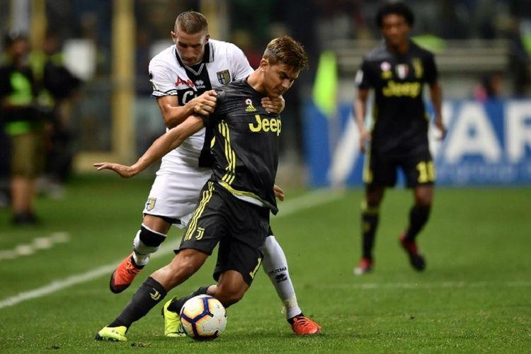 Penyerang Juventus, Paulo Dybala, dikawal gelandang Parma, Antonino Barilla, saat kedua tim bertandingan di Stadion Ennio Tardini, 1 September 2018.