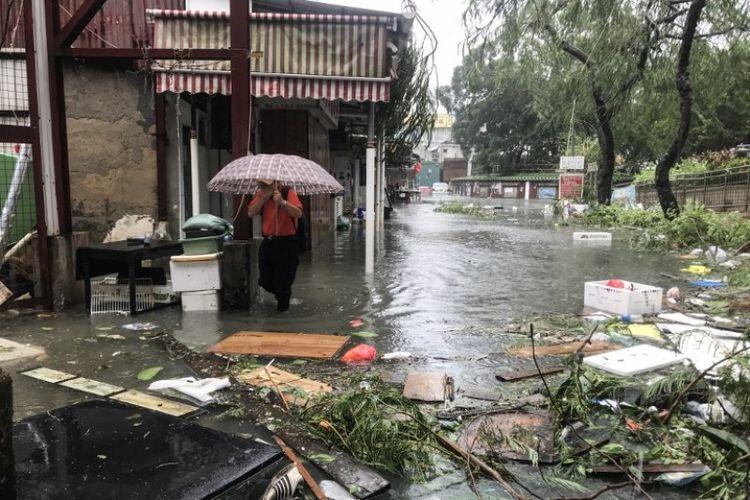 Seorang pria berjalan di tengah banjir di desa Lei Yu Man, setelah siklon tropis Mangkhut di Hong Kong pada Minggu (16/9/2018). (AFP/Anthony Wallace)
