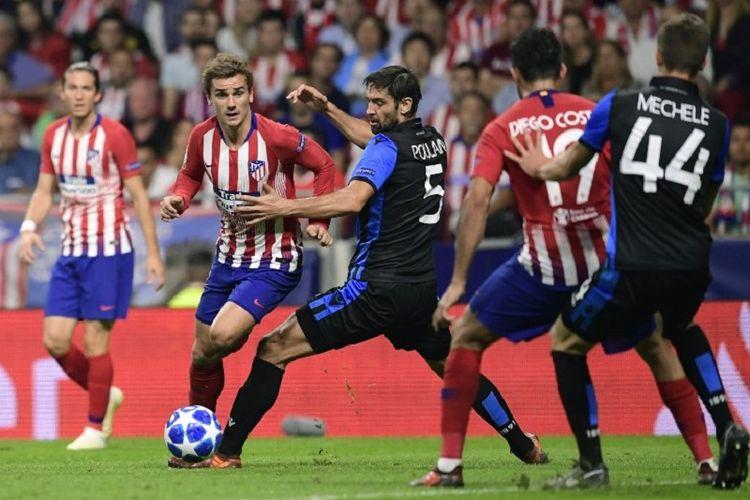 Antoine Griezmann mencoba melewati pengawalan Benoit Poulain saat Atletico Madrid vs Club Brugge beradu dalam lanjutan Liga Champions di Stadion Wanda Metropolitano, 3 Oktober 2018.