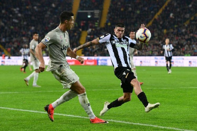 Rodrigo De Paul mencoba menutup pergerakan Cristiano Ronaldo saat Udinese vs Juventus beradu di Stadion Friuli, 6 Oktober 2018.