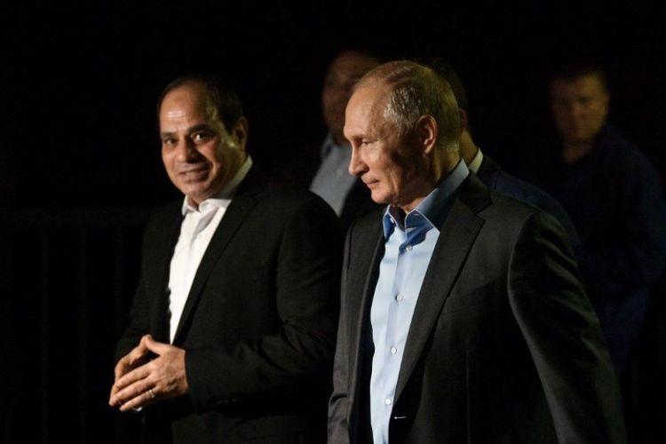 Presiden Rusia Vladimir Putin (kanan) dan Presiden Mesir Abdel Fattah Al-Sisi (kiri) berjalan di sepanjang tepi laut Olympic Park, di Sochi, Rusia pada Selasa (16/10/2018). (AFP/Sputnik/Alexei Druzhinin)