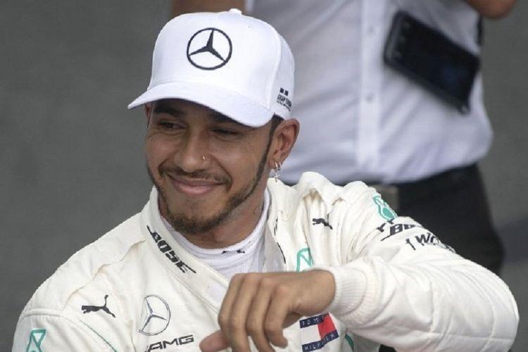 Pebalap Mercedes, Lewis Hamilton, merayakan keberhasilannya meraih pole position pada GP Brasil, 10 November 2018.