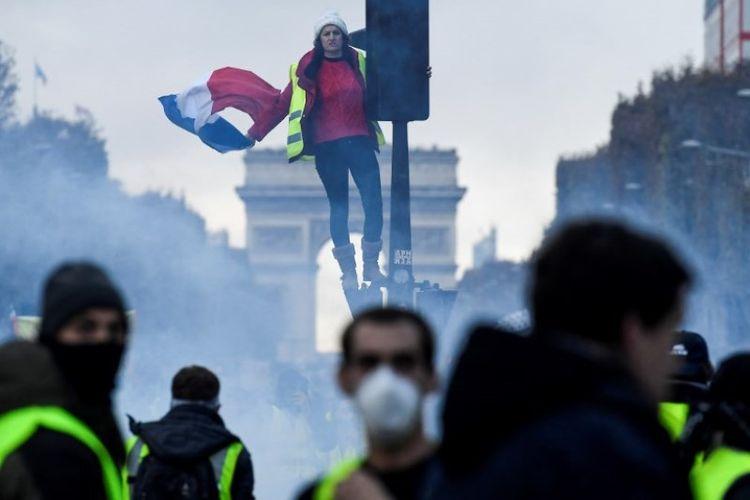 Seorang demonstran mengenakan rompi kuning memegang bendera Perancis saat berdiri di lampu merah di Champs Elysee, di Paris, Perancis, Sabtu (24/11/2018). Massa rompi kuning kembali berunjuk rasa untuk memprotes kenaikan harga minyak. (AFP/Bertrand Guay)