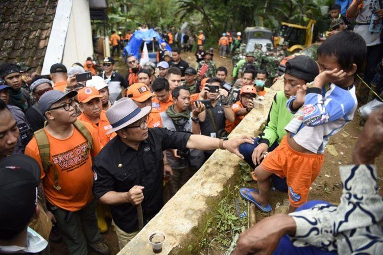 Gubernur Jawa Barat Ridwan Kamil saat berbincang dengan Hengki dan Farel di lokasi pengungsian korbam longsor Cisolok, Sukabumi, Rabu (2/1/2019).