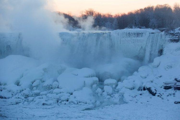 Uap muncul Air Terjun Niagara sebelum matahari terbit  di, Ontario, Kanada, Kamis (31/1/2019). Cuaca ekstrem membuat sebagian Air Terjun Niagara membeku. (AFP/Lars Hagberg)