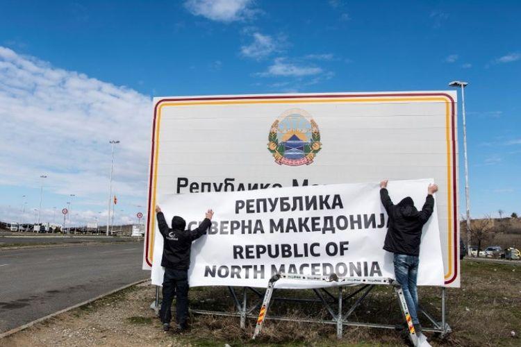 Masyarakat mengganti nama negara menjadi Republik Macedonia Utara pada tanda di perbatasan antara negara itu dengan Yunani di dekat Gevgelija, Rabu (13/2/2019). (AFP/ROBERT ATANASOVSKI)