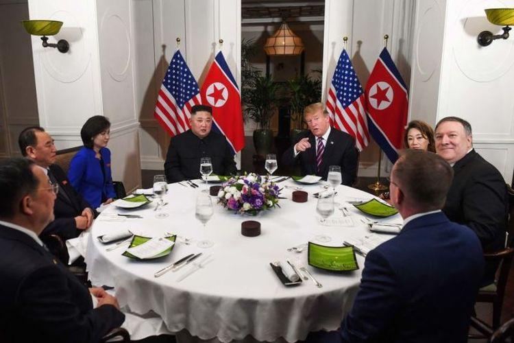 Presiden Amerika Serikat Donald Trump dan pemimpin Korea Utara Kim Jong Un duduk bersama bersama perwakilan lain dari masing-masing negara untuk makan malam di Hotel Sofitel Legend Metropole di Hanoi, Vietnam (27/2/2019). (AFP/SAUL LOEB).