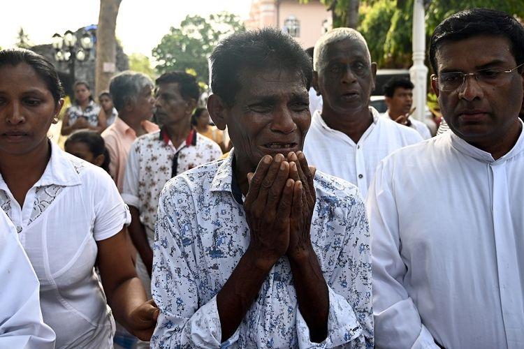 Seorang pria menangis sambil berjalan di belakang peti jenazah seorang korban bom Minggu Paskah usai misa di gereja St Sebastian, Negombo, Sri Lanka, Selasa (23/4/2019).