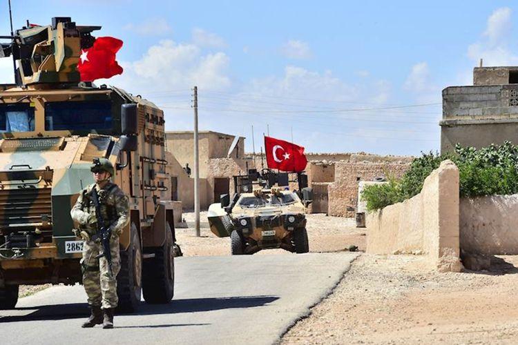 Foto yang dirilis Pasukan Bersenjata Turki memperlihatkan tentara Turki didampingi kendaraan lapis baja berpatroli di kota Manbij di Suriah utara, Senin (18/6/2018).