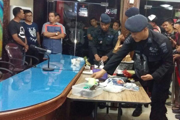 Petugas menyusun barang bukti sebelum Kapolda Riau Irjen Pol Nandang dan Rektor Universitas Riau Aras Mulyadi menggelar konferensi pers terkait penangkapan tiga terduga teroris dan penyitaan empat bom siap pakai dari gelanggang mahasiswa Universitas Riau, Sabtu (2/6/2018).