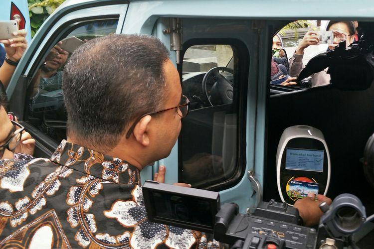 Gubernur DKI Jakarta Anies Baswedan menempelkan kartu OK Otrip ke mesin pembaca kartu yang ada di dalam angkot KWK dalam rangka uji coba OK Otrip di Balai Kota DKI Jakarta, Kamis (14/12/2017).