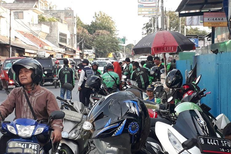 Tampak pengemudi Ojek Online di Jalan Raya Perjuangan dekat Stasiun Bekasi berjejer rapih memarkirkan kendaraannya di badan Trotoar, Minggu (16/9/2018).