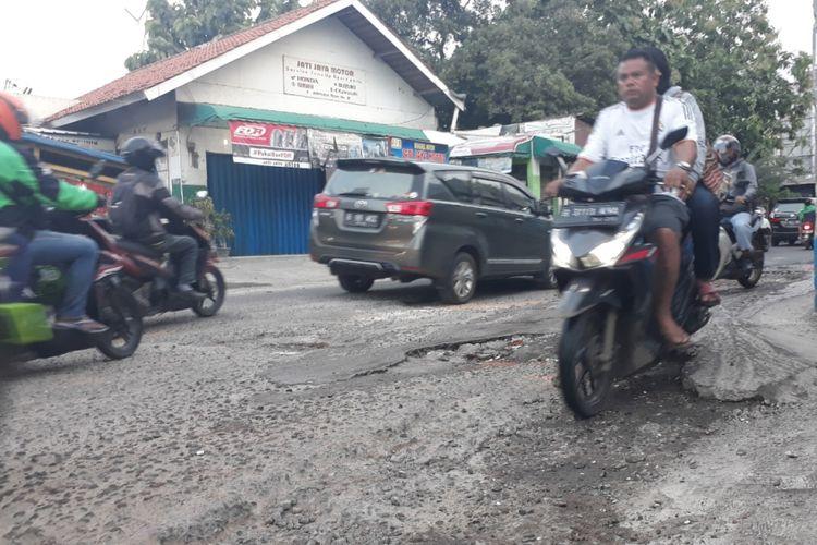 Tampak Jalan Raya Jatimulya, Pengasinan, Kecamatan Bekasi Timur, Kota Bekasi rusak dan berlubang menimbulkan kemacetan, Jumat (7/12/2018).