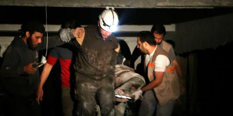 Petugas penyelamat Suriah ketika berusaha mengevakuasi korban serangan udara di Idlib Kamis 98/6/2018).
