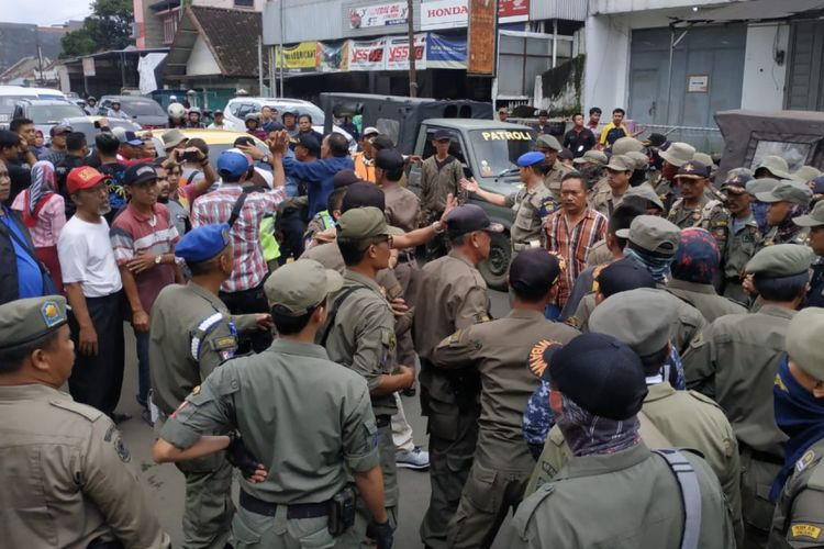 Anggota Satpol PP Sumedang bersitegang dengan PKL Jalan Tampomas, Sumedang, Jawa Barat saat penertiban, Selasa (5/3/2019) siang. AAM AMINULLAH/KOMPAS.com