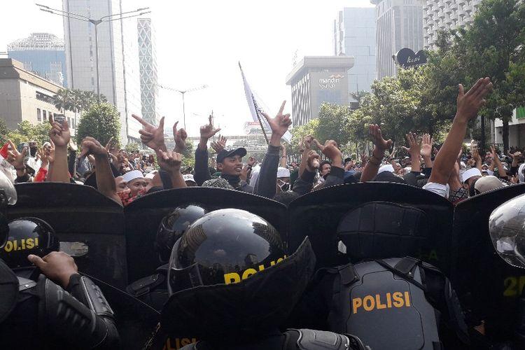 Massa peserta aksi 22 Mei menyanyikan yel-yel sambil mengacungkan dua jari di depan Djakarta Theatre, Rabu (22/5/2019).