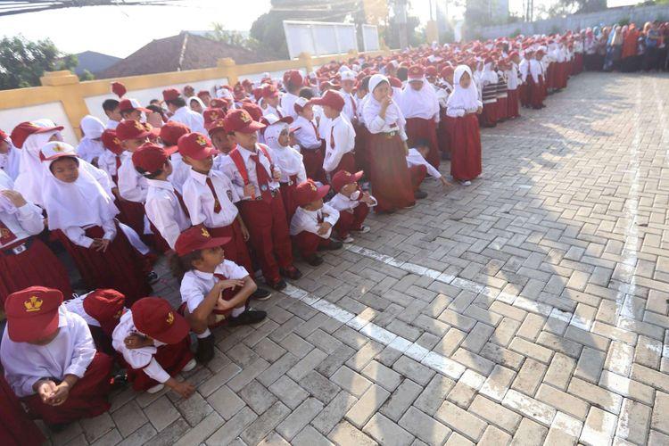Murid baru kelas 1 jongkok karena lelah mengikuti upacara di hari pertama masuk sekolah, di SD Negeri Lengkong Wetan 1, Serpong Utara, Tangerang Selatan, Senin (16/7/2018). Sebanyak 120 murid baru di SDN Lengkong Wetan 1 nampak diantar oleh orangtua pada hari pertama tahun ajaran baru 2018/2019