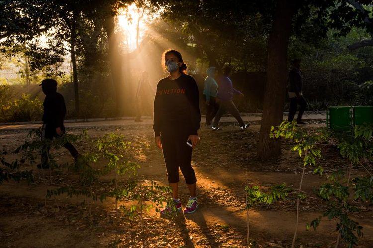 Seorang wanita muda memakai masker ketika berjalan-jalan di Taman Lordi pada pagi hari
