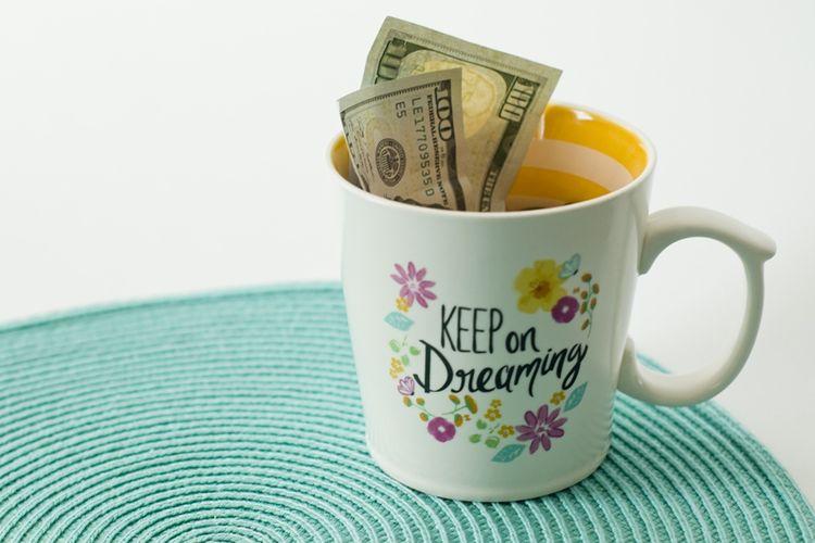Ilustrasi uang di dalam cangkir.