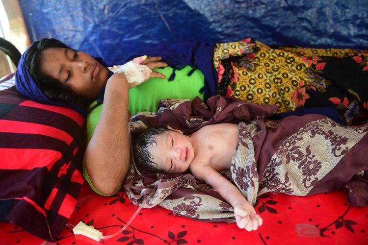 Gambar yang diambil pada 11 Oktober 2017 ini menunjukkan wanita Rohingya hamil Hasina Aktar terbaring di tempat tidur dengan bayinya yang baru lahir, Mohammed Jubayed di sebuah pusat medis di kamp pengungsi Kutupalong.