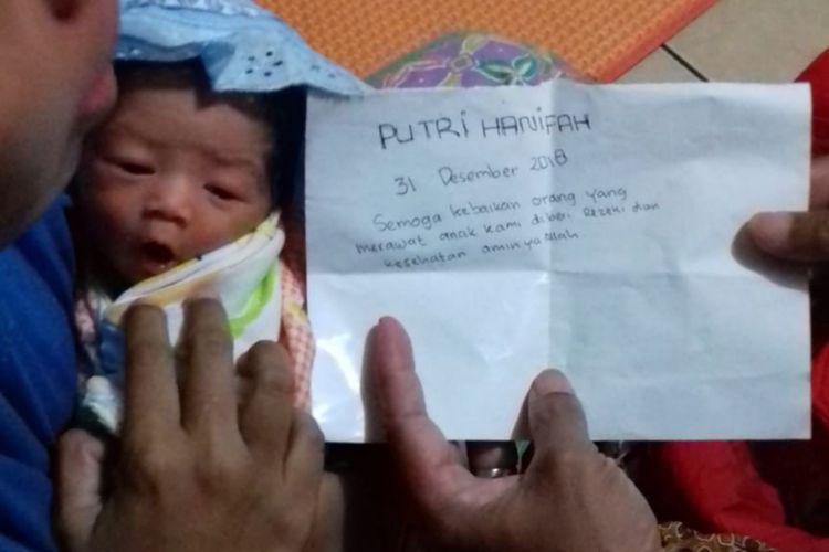 WARGA menunjukkan bayi malang dan sepucuk surat yang ditinggalkan orang tuanya di sebuah kandang sapi di Cikeruh, Jatinangor, Sumedang, Jawa Barat, Rabu (2/1/2019) malam sekitar jam 21.00 WIB.