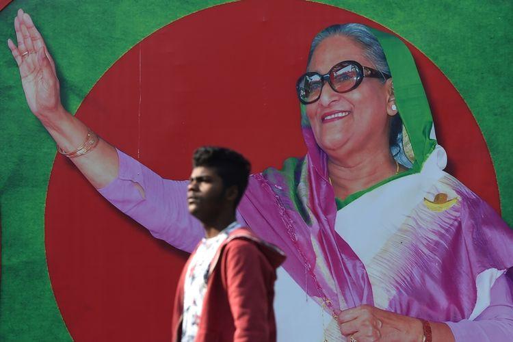 Pria Bangladesh berjalan melewati gambar Perdana Menteri Sheikh Hasina di Dhaka.
