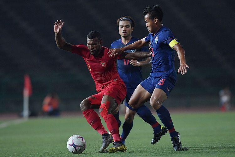 Pemain Timnas U-22 Marinus Wanewar (kiri) berebut bola dengan pemain Thailand Saringkan Promsupa (kanan) dalam pertandingan Final Piala AFF U-22 di Stadion Nasional Olimpiade Phnom Penh, Kamboja, Selasa (26/2/2019). ANTARA FOTO/Nyoman Budhiana/ama.