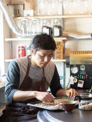 Fusuku-san yang memilih biji kopi dengan tangan di bawah sinar matahari pagi yang merupakan waktu paling baik untuk melihat kondisi biji