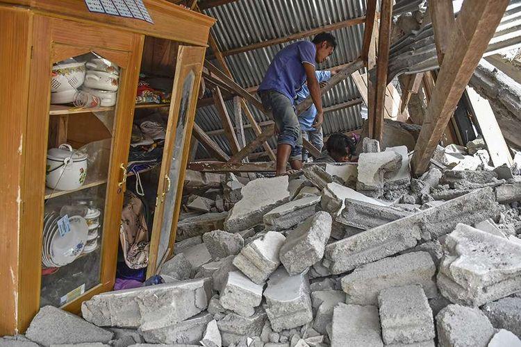 Warga mencari perlengkapan wisatawan asal Malaysia yang tewas tertimpa rumah roboh akibat gempa, di Desa Sajang, Kecamatan Sembalun, Selong, Lombok Timur, NTB, Minggu (29/7/2018). Data sementara BPBD Provinsi Nusa Tenggara Barat mencatat, gempa bumi berkekuatan 6,4 pada skala richter (SR) mengakibatkan delapan orang meninggal dunia, 10 orang luka berat, 10 orang luka ringan, dan puluhan rumah rusak di Kabupaten Lombok Timur.