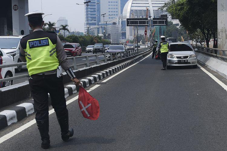 Petugas Ditlantas Polda Metro Jaya memberhentikan mobil berpelat nomor genap yang memasuki Jalan Gatot Soebroto, Jakarta, Rabu (1/8/2018). Petugas kepolisian mulai memberlakukan penindakan berupa tilang terhadap pengendara mobil yang melanggar di kawasan perluasan sistem ganjil-genap.