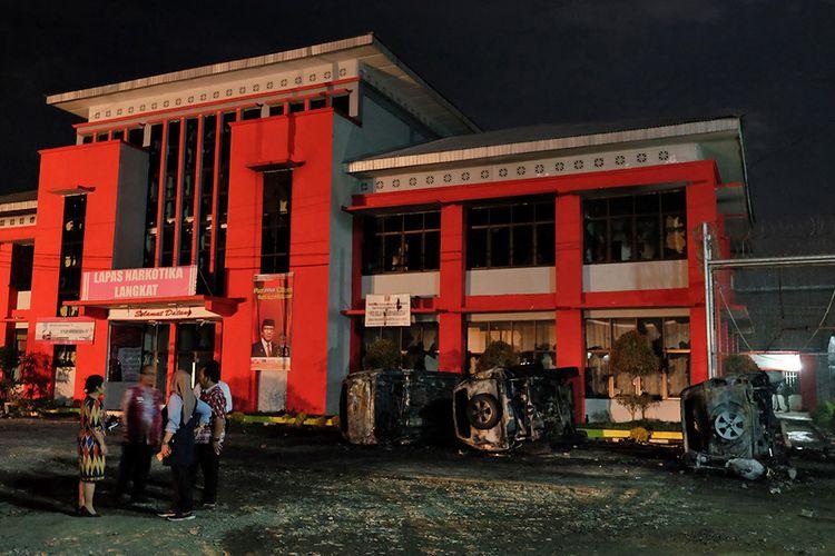 Petugas Lapas berada di depan Lapas Narkotika Kelas III Langkat pasca-kerusuhan yang terjadi, di Langkat, Sumatera Utara, Kamis (16/5/2019). Akibat peristiwa kerusuhan yang dilakukan para narapidana di Lapas tersebut mengakibatkan tiga mobil petugas rusak terbakar dan ratusan napi melarikan diri.