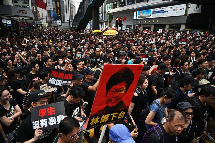 Poster bergambar Chief Executive Hong Kong Carrie Lam terlihat di antara ribuan peserta unjuk rasa yang memenuhi jalanan Hong Kong dalam aksi menentang UU Ekstradisi, Minggu (16/6/2019). Aksi protes itu dimulai ketika Hong Kong, bekas koloni Inggris yang kembali kepada China berdasarkan satu negara, dua sistem pada 1997, memperkenalkan UU Ekstradisi.