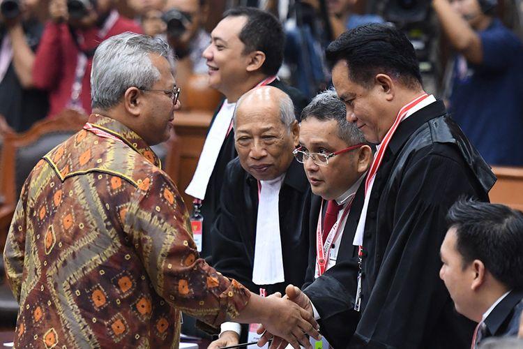 Ketua KPU Arief Budiman (kiri) selaku pihak termohon berjabat tangan dengan Ketua tim kuasa hukum pasangan calon presiden dan calon wakil presiden nomor urut 01 Yusril Ihza Mahendra (kedua kanan) selaku pihak terkait sebelum mengikuti sidang lanjutan Perselisihan Hasil Pemilihan Umum (PHPU) Pilpres 2019 di Gedung Mahkamah Konstitusi, Jakarta, Selasa (18/6/2019). Sidang tersebut beragendakan mendengarkan jawaban termohon, pihak terkait dan Bawaslu.