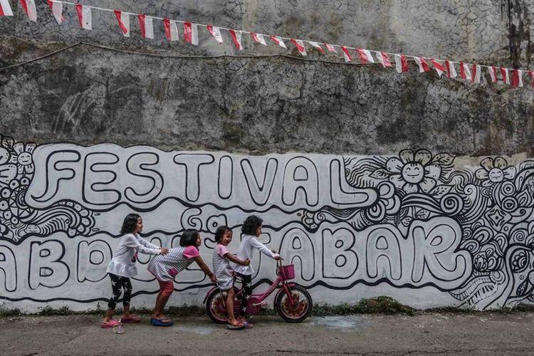 Anak-anak sedang bermain-main di depan mural bertuliskan Festival Gang Abdul Jabar yang akan diisi warna dan ornamennya oleh teman-teman sebayanya pada sore hari 19 Agustus 2017.