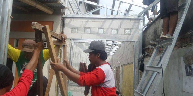 Pasukan merah dan petugas PPSU sedang melakukan pemasangan atap dan tembok di rumah-rumah yang termasuk dalam program bedah rumah yang dicanangkan Pemprov DKI Jakarta, Jumat (5/5/2017).